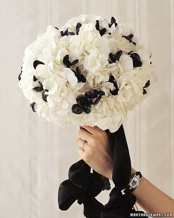Glossy blackbeaded flowers dance among puffs of white hydrangeas in a lush